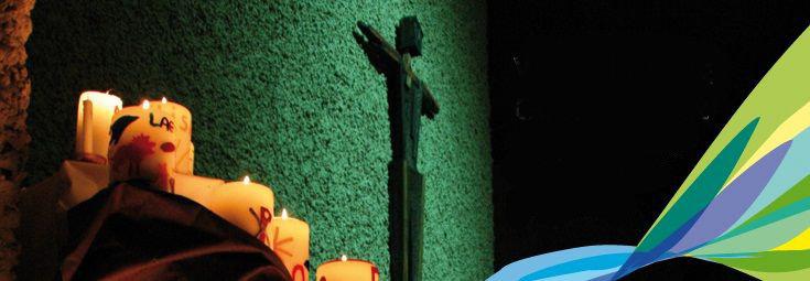 Bild: Grüne Wand mit Kreuz davor und brennde selbstgestaltete Kerzen; Quelle: KB-Hochrhrein